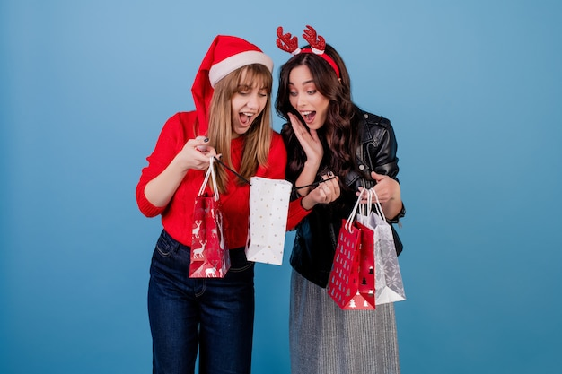 Women with presents in colorful shopping bags wearing christmas hat and winter clothes isolated over blue