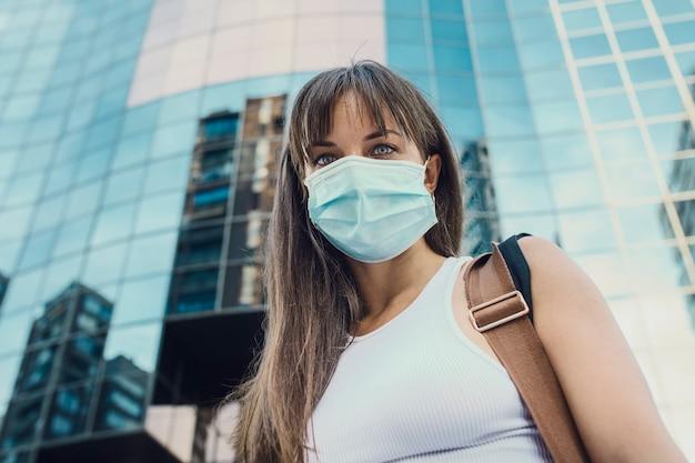 Женщины с профилактической маской от вируса короны на фоне офисных зданий. концепция вируса короны на работе или учебе.