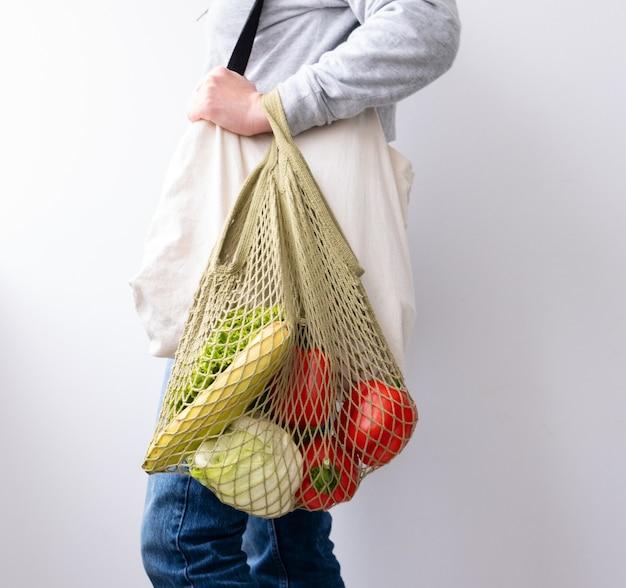 ショッピング用の再利用可能な綿とメッシュのエコバッグを持つ女性。