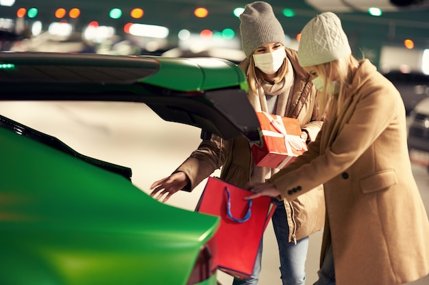 Women with shopping bags and christmas presents in masks in underground parking lot