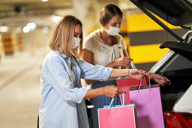 Женщины с сумками в масках на подземной автостоянке