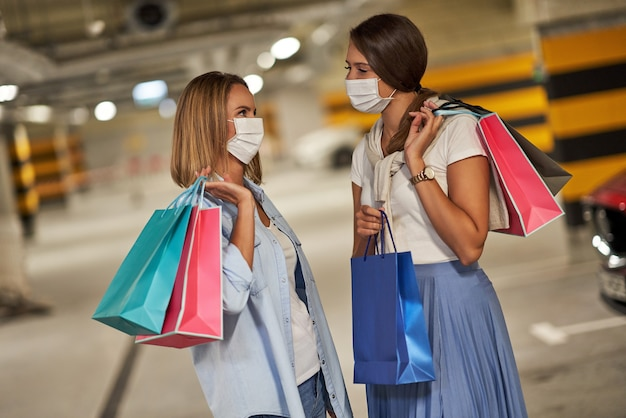 Women with shopping bags in masks in underground parking lot
