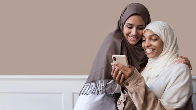 Donne con smartphone colpo medio