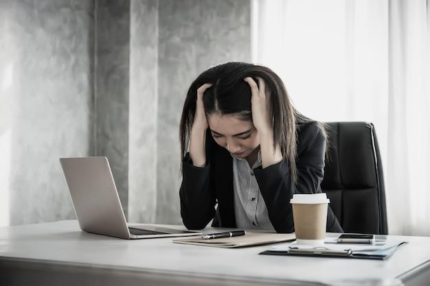 Женщины со стрессом руки на голове, думая с новым проектом на рабочем месте.