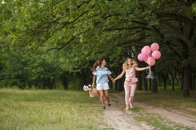 Women with a wicker basket, hat, pink balloons and flowers runing on a country road