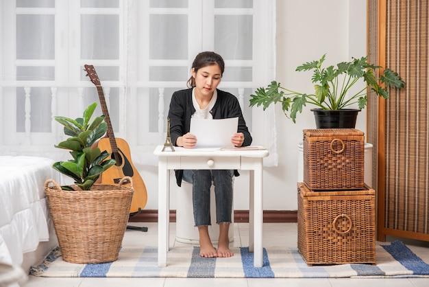 女性はテーブルで働き、文書を分析します。