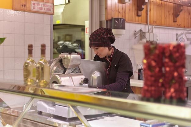 Women work in the butcher's fridge counter taking meat cuts