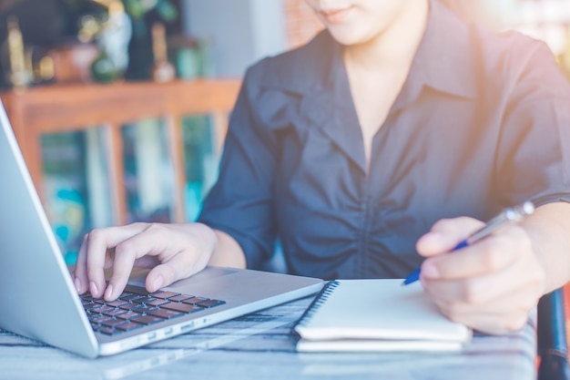 Women work with laptops and take notes in notebooks in the office.