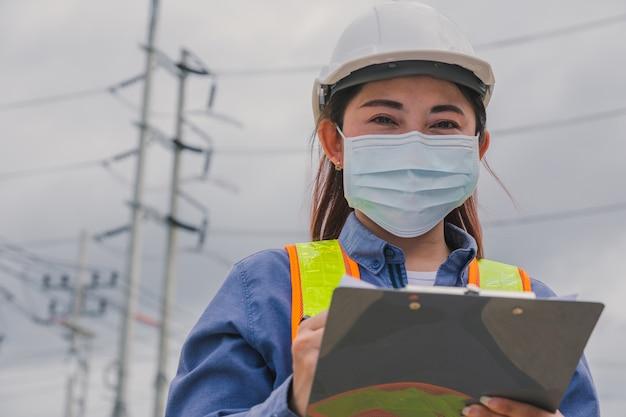 Работницы женщины носят маску для лица, держа опрос работы буфера обмена