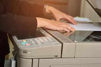 女性労働者はオフィスで複写機を使用しています。