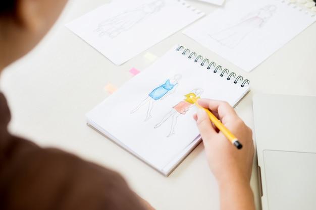 ファッションデザイナーとして働く女性は、職場のスタジオでアトリエ紙で服のスケッチを描く。