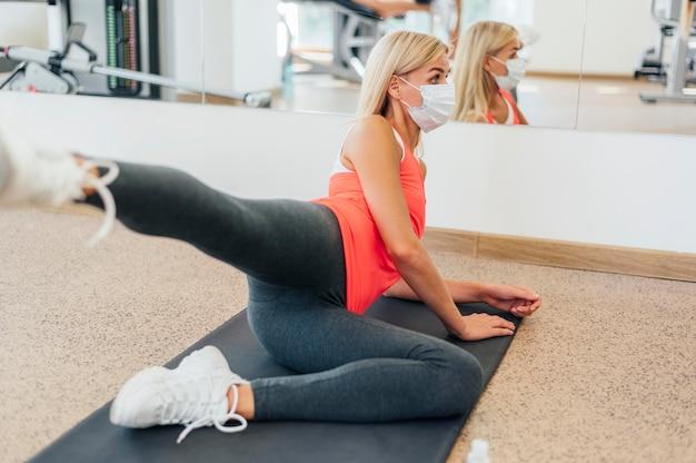 医療マスクでジムで運動している女性