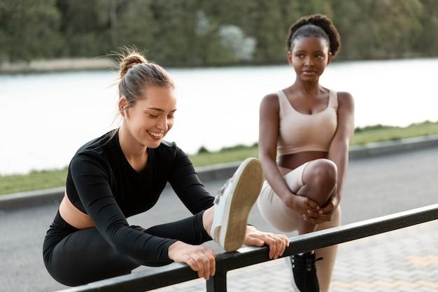 屋外で一緒に運動する女性