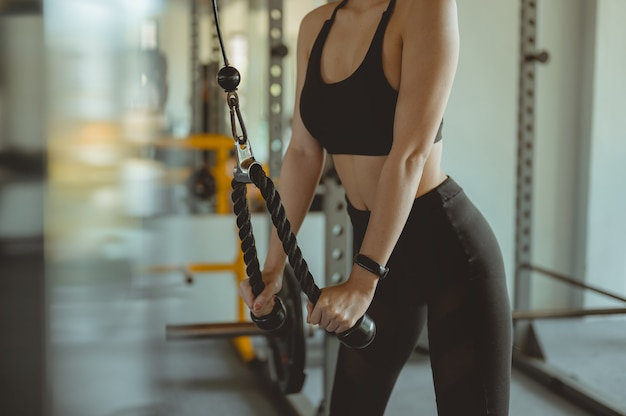A women working out training arms in gym gaining weight pumping up muscles with dumbbells