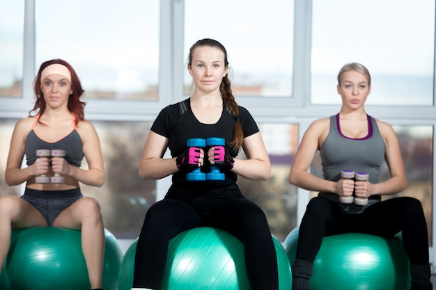 Women working out with dumbbells on balls