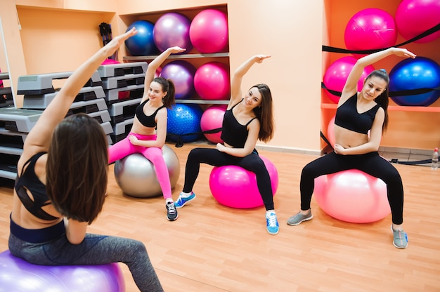 Women working out with exercise ball in gym