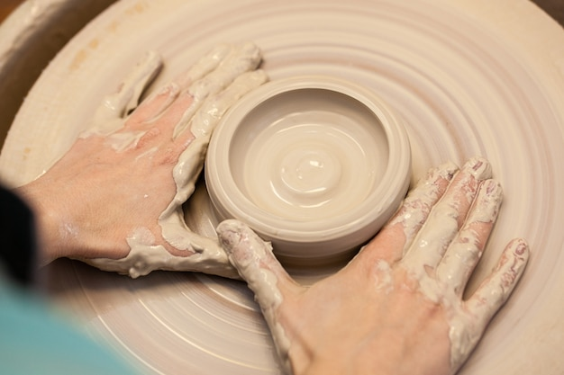 Women working on the potters wheel close up