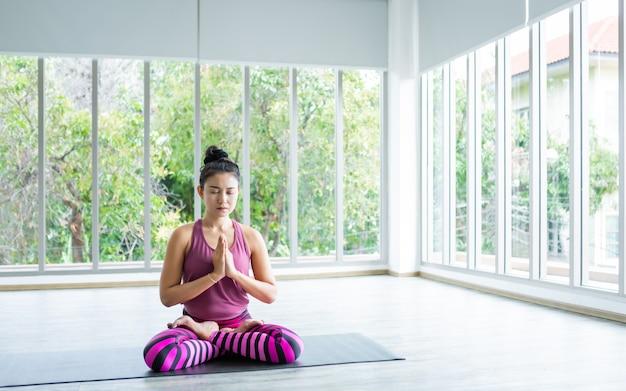 ピンクの服を着て瞑想を練習するヨガトレーニングを練習する女性のトレーニング