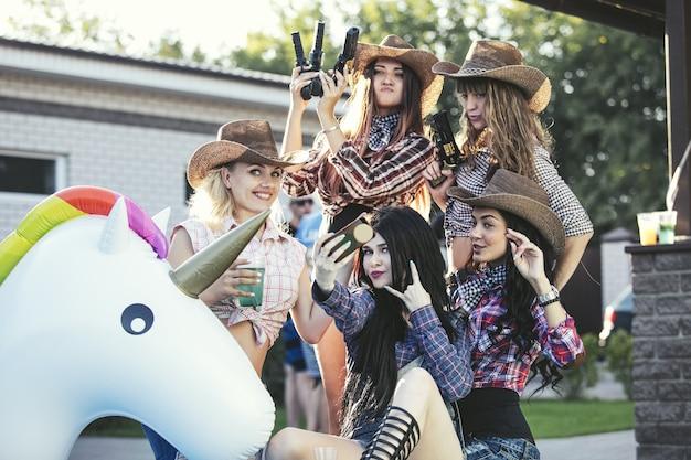 カウボーイスタイルで一緒に飲み物とパーティーで若い美しい官能的な楽しみの女性