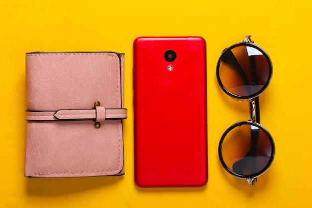 黄色のレディースアクセサリーとガジェット。財布、スタイリッシュなラウンドサングラス、黄色のスマートフォン