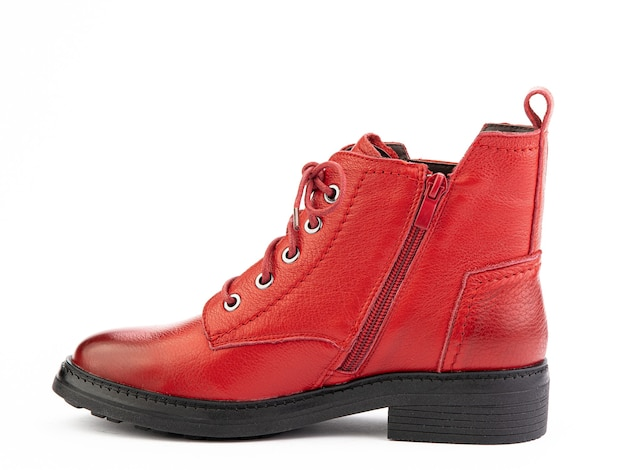 白い背景の左側面図に分離された黒い靴底と女性の秋の赤い革ジョッパーズブーツ