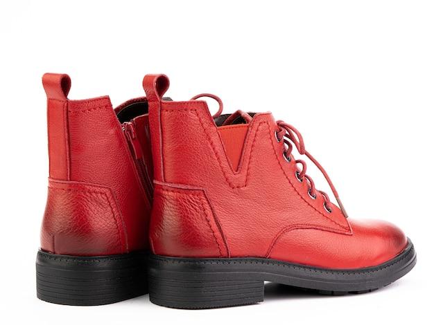 白い背景で隔離の黒い靴底と女性の秋の赤い革ジョッパーズブーツ