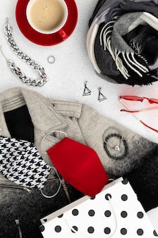 Womens autumn winter clothes look with protective mask on gray table. flat lay top view new normal fashion composition.