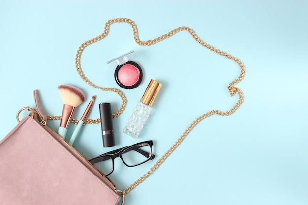 色付きの背景にレディースバッグと化粧品