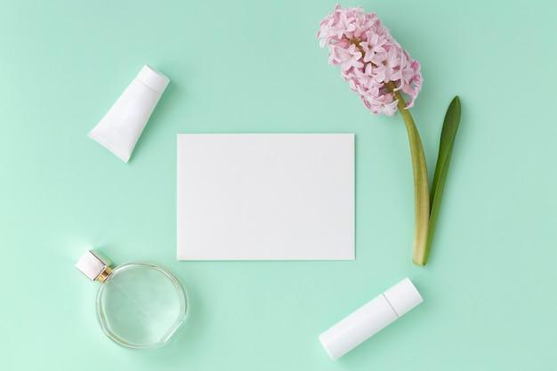 女性の美しさと春のコンセプト。ギフトセット、モカップ。封筒、香水瓶、化粧品チューブ、ヒヤシンスの花。