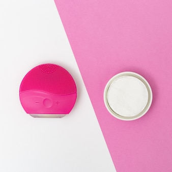 Womens beauty and hygiene products, red elecrtic face brush and cotton pads on white and pink paper background. facial treatment. flat lay style. top view.