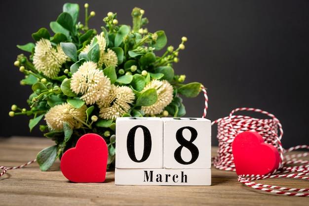 コピースペースと女性の日の背景花のカレンダーと木製のテーブルの上の心