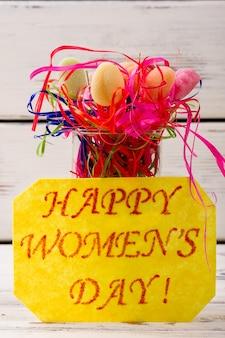 女性の日カードとキャンディーストリーマースイーツとグリーティングペーパー春の休日のためのおいしいレシピ