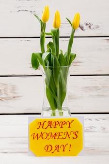 カードの近くの花瓶の女性の日カードとチューリップの花は、妻の手作りの春の贈り物に素敵な驚きを作ります
