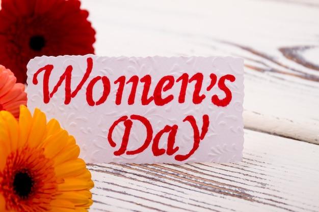 ガーベラの生花とグリーティングペーパーの近くの女性の日カードはあなたのガールフレンドを祝福します