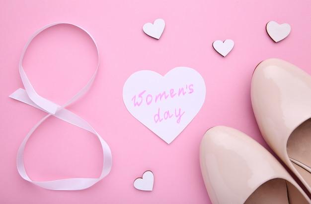 ピンクの背景のアクセサリーと女性の日の概念