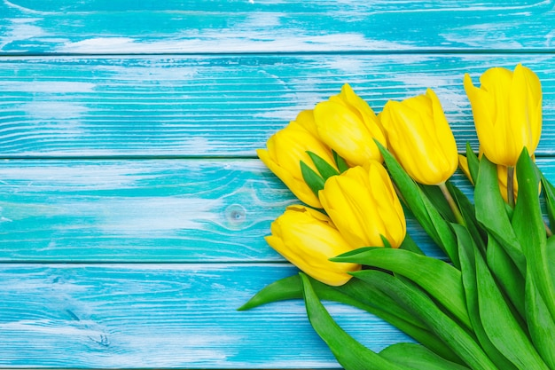 Womens day. tulips bouquet on wooden planks background, copy space, top view
