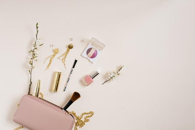 ピンクのバッグまたはベージュの背景にスペースアップルツリーの花をコピーした化粧品バッグの隣にある化粧品の女性用デスク