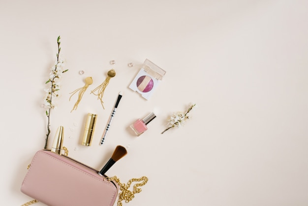 Womens desk with cosmetics which lies next to a pink bag or cosmetic bag with copying space apple tree flowers on a beige background