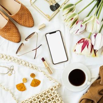レディースファッション美容ブログホームオフィスデスク。空白の画面の携帯電話、チューリップの花の花束、服やアクセサリー