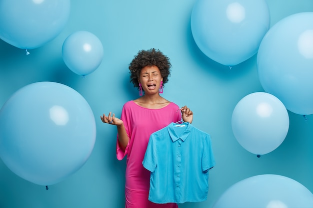 レディースファッションコレクションのコンセプト。落ち込んで泣いている暗い肌の女性は、ワードローブで服を整理し、ハンガーに青いシャツを着て、機嫌が悪い、パーティーに何を着るかを考える、青い壁