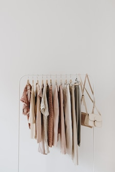 Womens fashion pastel clothes. stylish female blouses, sweaters, pants, jeans, tshirts, handbags on hanger on white.