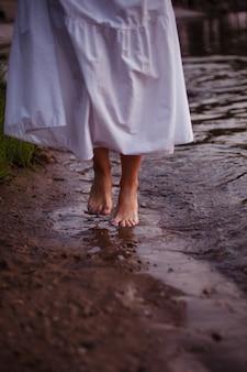長い夏のサンドレスを歩いている女性の足の川のクローズアップ正面図の女性の足...