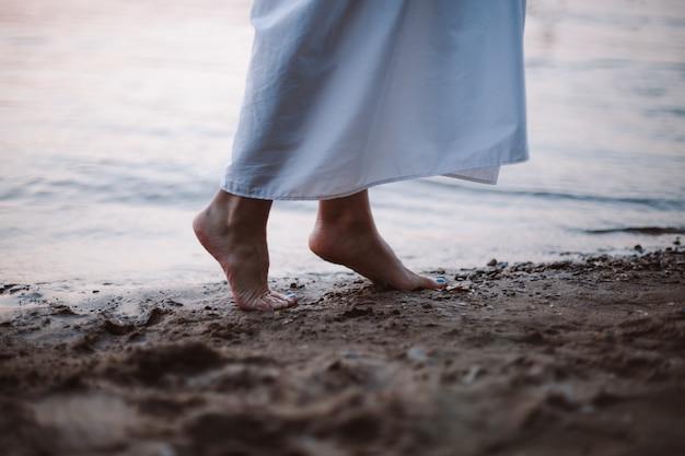 日没時の砂浜の川のビーチで若い女性の素足の川のクローズアップの側面図の女性の足