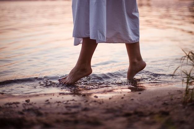 Женские ноги в речном образе жизни крупным планом на ногах женщины в длинном белом платье, идущей в одиночестве ...