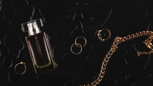 Womens gold accessories and perfume on a black background among water drops top view flat lay layout