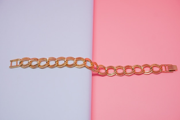 Womens gold chain bracelet with peach color background