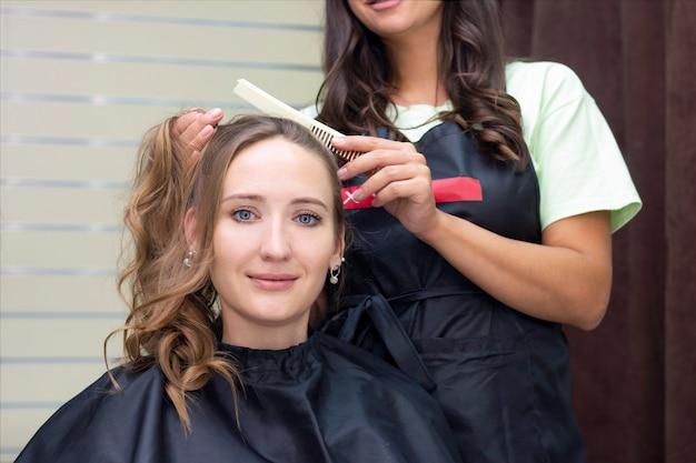 Женский парикмахер, салон красоты. крупным планом парикмахер делает прическу.