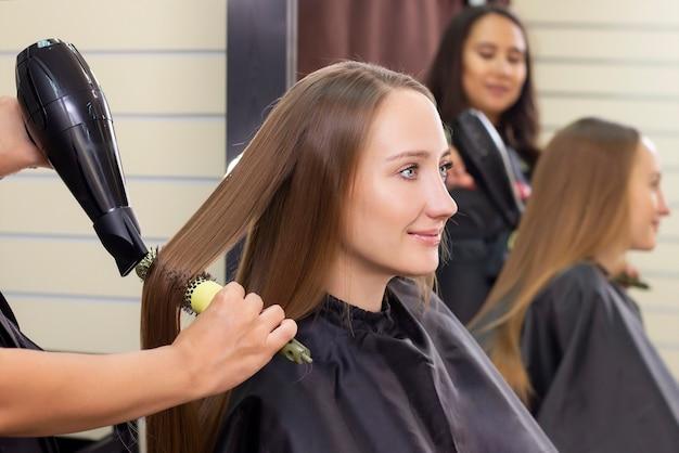 Женский парикмахер, салон красоты. сушка волос феном и круглой щеткой.