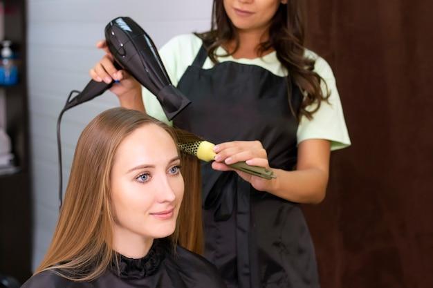 レディース美容院、美容院。ヘアドライヤーと丸いブラシで髪を乾かします。