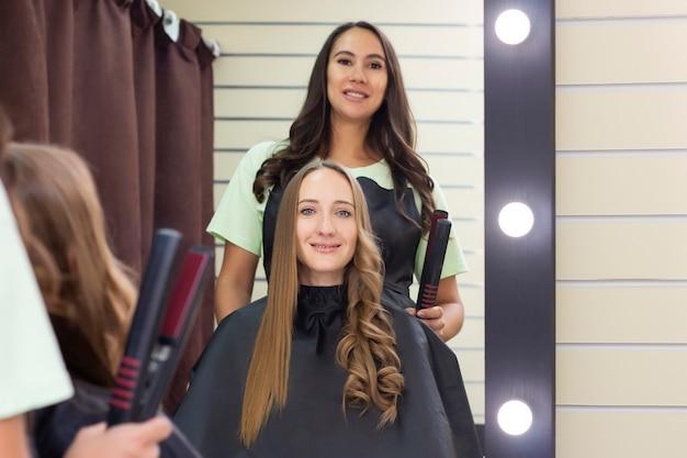Женский парикмахер, салон красоты. парикмахер делает кудри плойкой Premium Фотографии